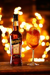 An Aperol spritz and bottle of Aperol on a table in front of warm Christmas lighting.